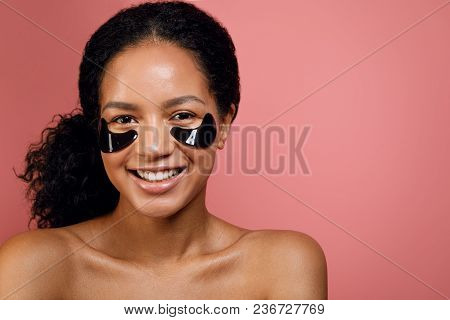 Studio Portrait Of A Happy Mixed Race Woman With Under Eye Mask On Her Face