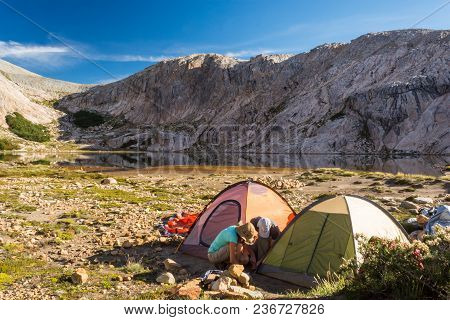 Man And A Woman Making A Camping Tent At A Remote Campsite In The Wilderness Of The Mountains, After