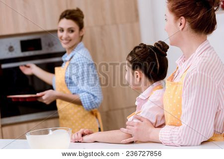 Three Generations Of Beautiful Women In Aprons Baking Pastry Together At Kitchen