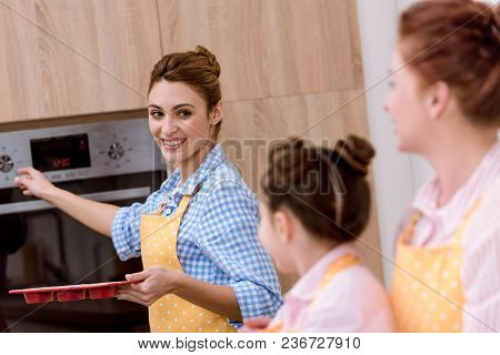 Three Generations Of Women Baking Pastry Together At Kitchen
