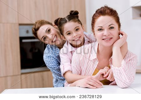 Three Generations Of Happy Beautiful Women Standing In Row Together At Kitchen And Looking At Camera