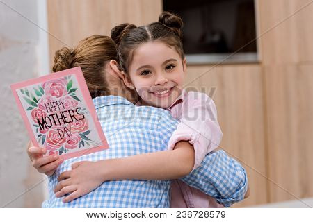 Mother Embracing Her Daughter While She Holding Mothers Day Greeting Card
