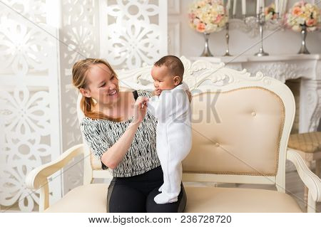 Loving Mother Holding Mixed Race Baby Boy At Home.