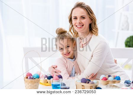 Mother And Daughter Embracing By Table With Painted Easter Eggs