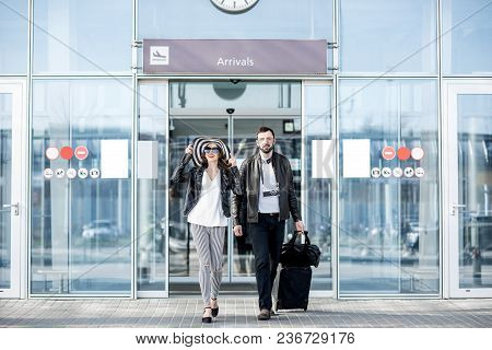 Young Couple Walking Out The Airport With Luggage During The Honeymoon