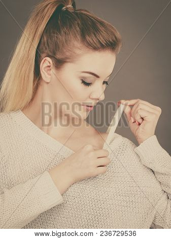 Woman Holding Her Bra Strap From Under Her Sweater. Brafitting Concept. Grey Background.