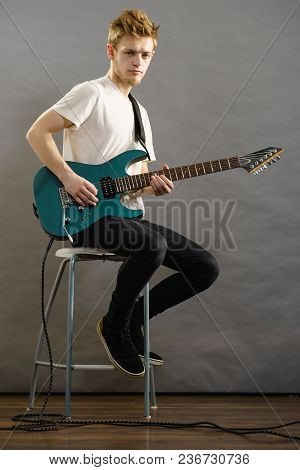 Young Bearded Man With Electric Guitar. Adult Person Is Holding Instrument And Playing. Hobby, Music