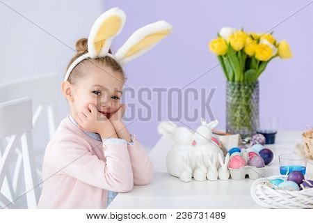 Kid In Bunny Ears By Table With Easter Eggs