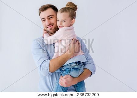 Father Embracing Little Daughter Isolated On Blue