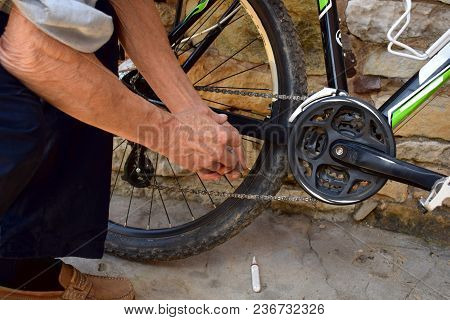 A Man Lubricates A Bicycle Chain With An Exploding Syringe.