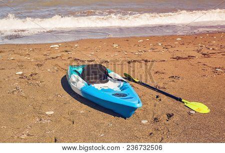 Blue Kayak Lying On The Sandy Beach.