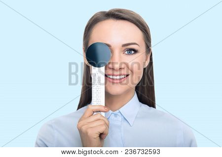 Smiling Woman, Checking Vision, Closing Eye With Special Tool, Blue Background. The Vision Test Conc