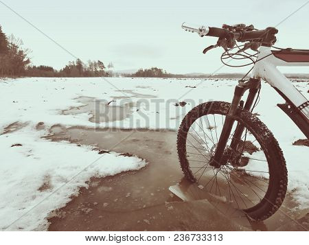 Bike Drowned In Muddy Pool Within Winter Trip. Broken Pieces Of Ice Around Freeze Terain Tyre, Wide