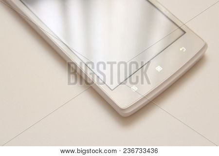 White mobile phone isolated on white background. Phone on the table. Shiny phone screen. Sparkling new smartphone.  Talking on the mobile phone