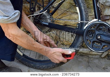 A Man Cleans A Bicycle Chain With A Brush.
