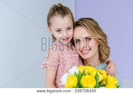 Cute Child Embracing Mother With Tulips Bouquet On 8 March