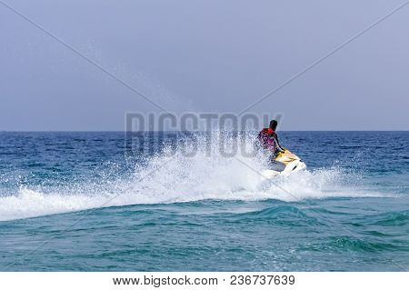 Summer Entertainment At The Sea. Tourists Riding A Jet Ski. Sea Time. Summer Holidays At The Seaside