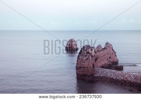 Beautiful Atlantic Ocean View Horizon With Sandy Beach, Rocks And Waves At Sunrise. Algarve, Portuga