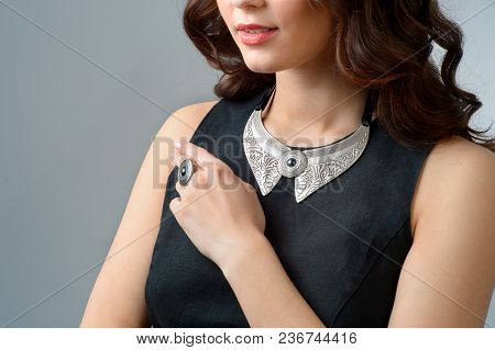 Close-up Woman Hand With Ring On Finger And Necklace On A White Background