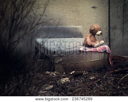 A Toy Bear On An Old Discarded Bed In A Dull Place. The Concept Of Homelessness, Uselessness, Depres