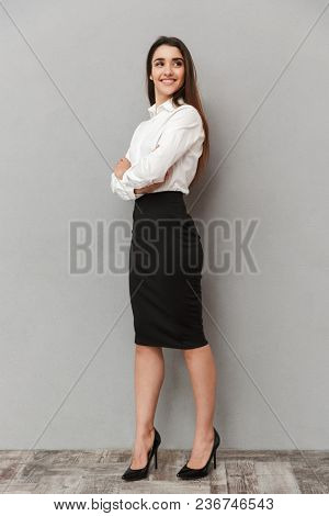 Full length portrait of successful young woman 20s with long brown hair in business wear smiling at camera and keeping arms crossed isolated over white background