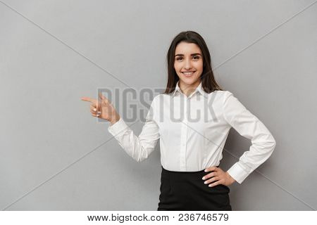 Portrait of beautiful woman with long brown hair in white shirt smiling and pointing finger aside on copyspace isolated over gray background