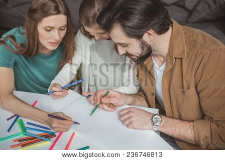 High Angle View Of Parents And Daughter Drawing With Felt-tip Pens