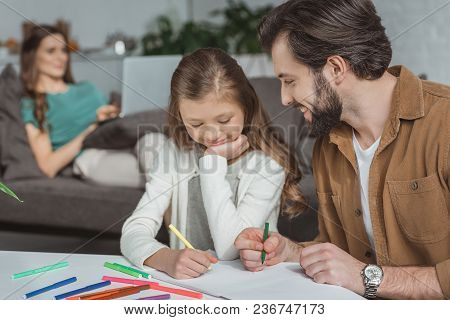 Father And Daughter Drawing With Felt-tip Pens In Album