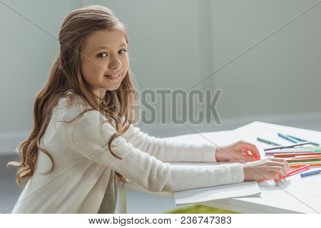 Side View Of Adorable Kid Drawing With Felt-tip Pens At Home