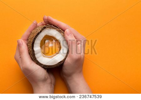 Female Hands Holding Coconut Half With Egg Yolk Inside On Yellow Studio Backdrop. Appearances Are De