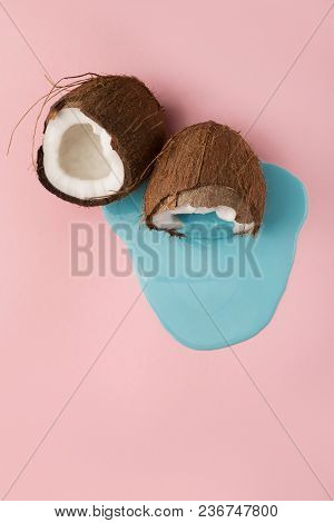 Blue Paint Flowing From Coconut Half On Pink Table. Creative Background With Copy Space, Bold Design