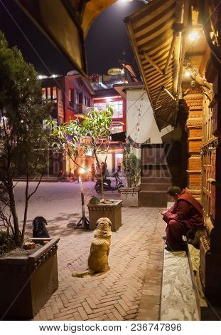 The Buddhist Monk Looks At The Screen Of The Smartphone, Sitting On Stairs Of Houses In An Environme
