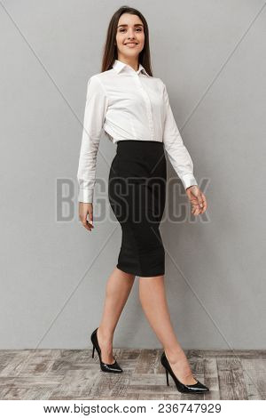 Full length portrait of adorable young woman 20s with long brown hair in white shirt and black skirt posing at camera with smile isolated over white background