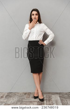 Full length portrait of emotional woman with long brown hair in business wear covering mouth in astonishment or surprise isolated over white background