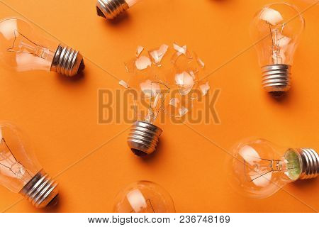One Broken Light Bulb Among Whole Ones On Yellow Background, Side View, Closeup. Creativity And Frag