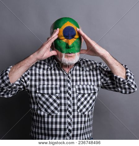 Portrait Of Sad Senior Man With Flag Of Brasil Painted On His Face. Football Or Soccer Team Fan Hand