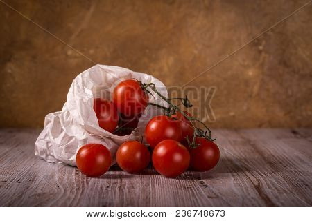Juicy Fresh Red Tomatoes On Wooden Board In Paper Bag