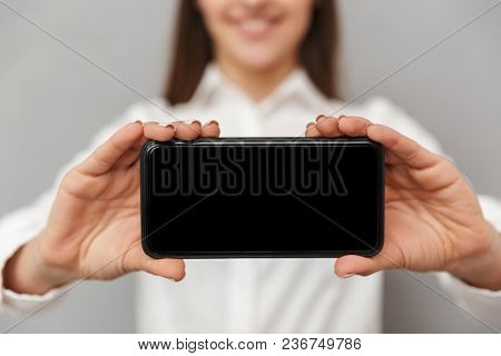 Blurry photo of smiling woman with long brown hair holding cell phone and advertising black copyspace screen at camera in focus closeup isolated over gray background