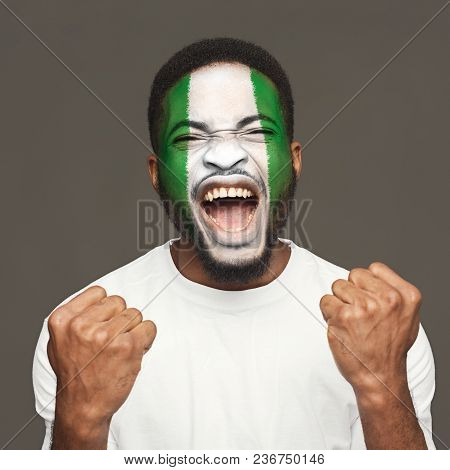 Face Of Young Screaming African-american Man Painted With Flag Of Nigeria. Football Or Soccer Team F
