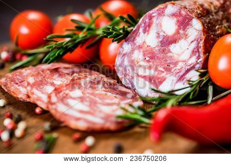 Close Up Image Of Cured Sausage On Wooden Board With Fresh Tomatoes, Herbs And Peppercorn. Selective