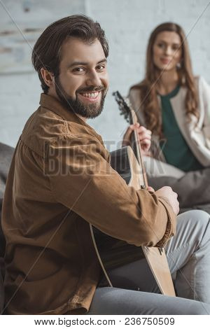 Smiling Boyfriend Playing Guitar And Looking At Camera At Home