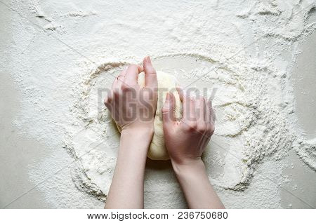 Woman Hands Kneads The Dough With Flour On The White Kitchen Table. Top View Flat Lay. Copy Space Fo
