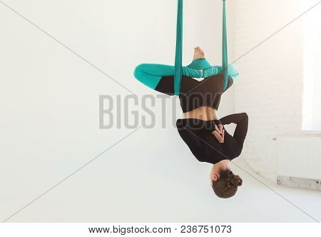 Caucasian Woman Practicing Fly Yoga Bat Asana Over White Background In Fitness Studio, Copy Space, B