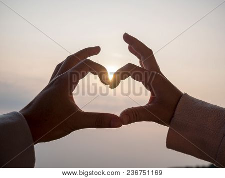 The Hand Of The Couple Is Heart Shaped. Along The Background Of The Sky And The Sun