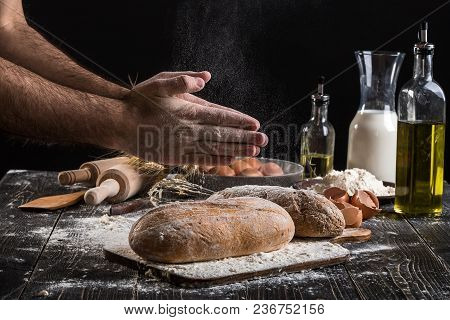 Chef Sprinkles Fresh Bread With Flour. Man Preparing Dough At Table In Kitchen. On Black Background.