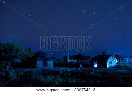 Long exposure shot of African village at night with star trails.