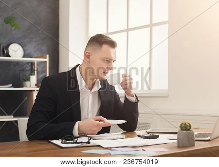 Young Businessman Working With Papers And Drinking Coffee In Modern Office Interior. Handsome Man, S