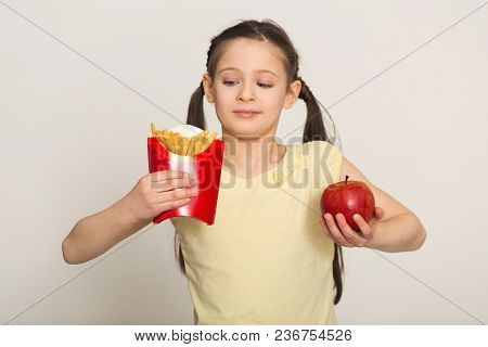 Hesitated Little Girl Holding A Bag Of Fries And Apple Isolated On White Background. Fast Food Again