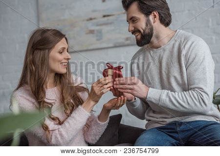 Side View Of Boyfriend Presenting Gift To Girlfriend On 8 March At Home