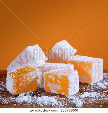 Orange Turkish Delight. Oriental Sweets Lukum On A Yellow Background. Close-up.